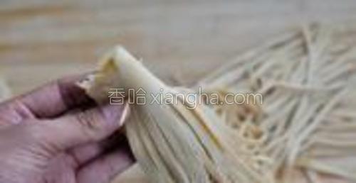 沿着没切的那部分把豆腐丝卷好,用牙签扎上固定。