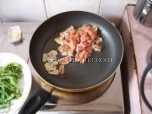 另起锅下油爆香蒜片,下肉片快速划散。