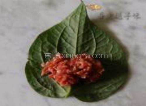 把适量的肉馅放在叶背上。
