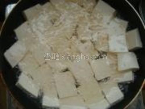 锅中加油烧热放入豆腐块煎。