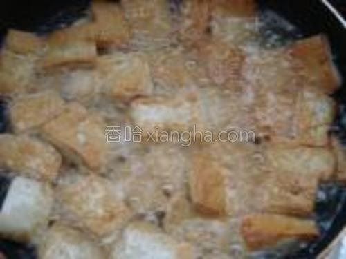 豆腐煎至两面金黄时捞出沥油。
