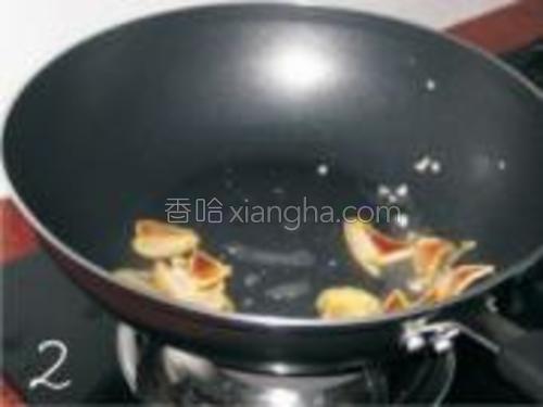 锅内热油先放一半的蒜米,然后爆炒腊肉。