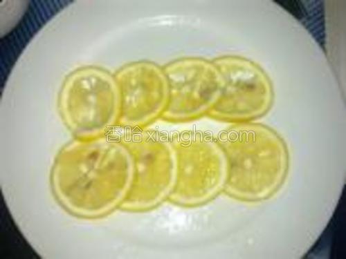 将其中一个柠檬洗净切成薄片均铺在盘中。