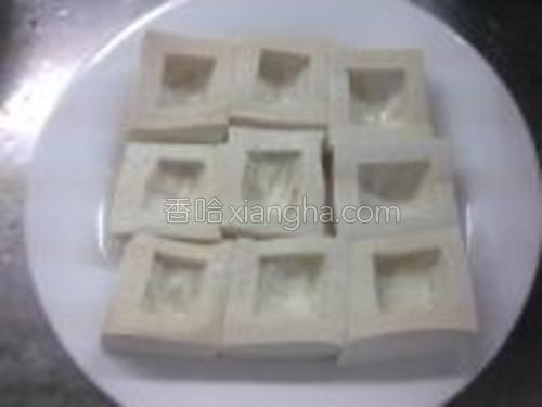 在豆腐上用小勺挖出洞,撒入盐、生粉。