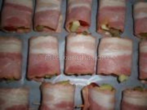 烤盘上铺油纸,卷好的培根卷依次码好。
