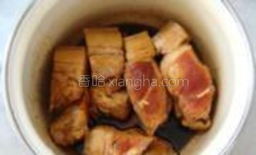 将肉块放入锅中,加入适量料酒和酱油腌制;