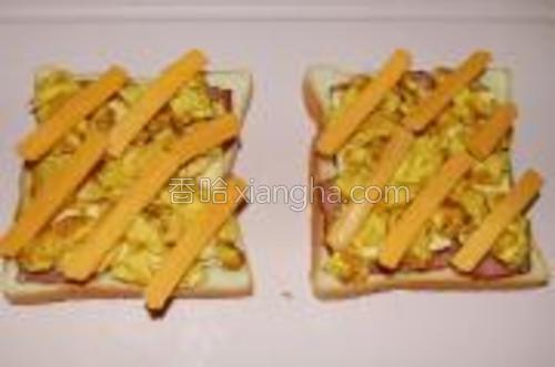 将车打奶酪切成条,铺在鸡蛋块上。