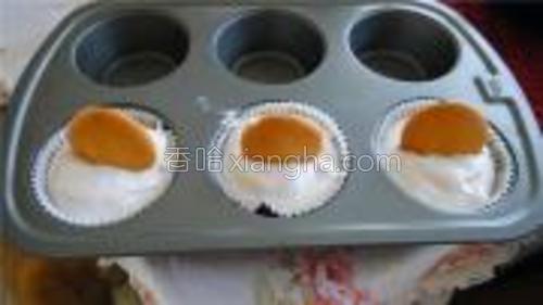 将搅拌后的奶油酸奶平均分入3个烘培纸内,然后没一个上面插一片威化饼干,放入冰箱冷冻1小时。