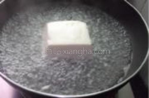豆腐放开水锅里烫下,捞起装盘,备用。
