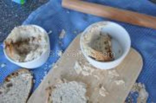 分成两半,塞到小杯子容器里。用手指把面包往杯壁上压压紧。