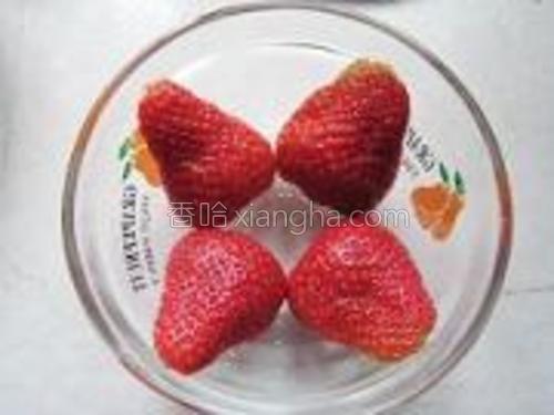 将对半切开的草莓铺在碗底。