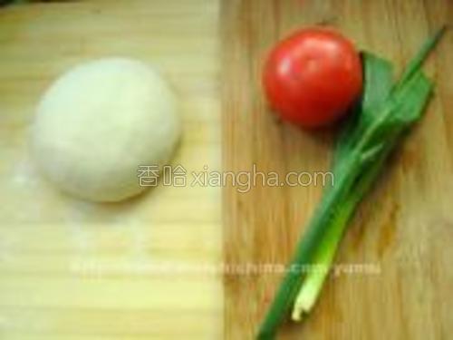 将面加凉水,揉成有点硬的面团,醒15分钟备用。准备一个西红柿和葱叶。