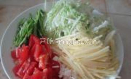 将大葱和包包菜,青辣椒洗净青椒切成丝土豆去皮切成丝,西红柿切成块