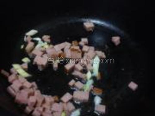 锅内倒入少许油,放入葱末翻炒后倒入火腿。
