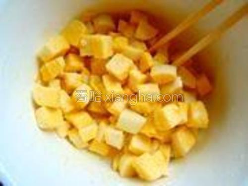 用筷子轻轻地翻动馒头丁,使每一块馒头丁都沾上蛋液。