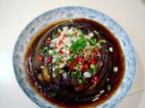 在茄子上撒上红椒末、香葱末和蒜末。