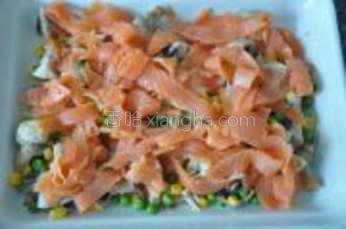 然后捞出蔬菜,将熏三文鱼切条,铺再蔬菜上。