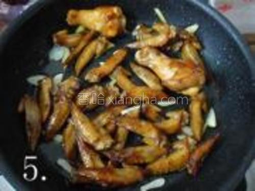 锅里留余油,爆香姜蒜末之后,再把煎好的鸡尖放入翻炒。
