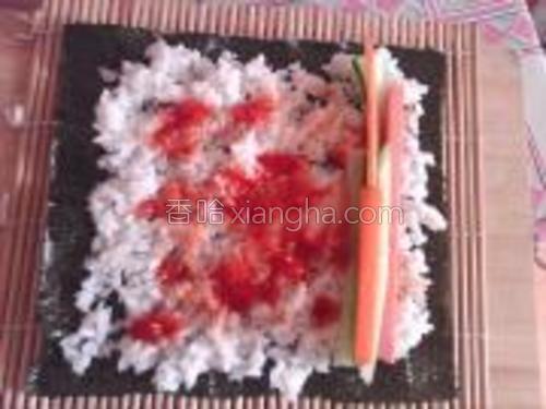 取出寿司帘和紫菜,把紫菜滑面向下放在寿司帘上,在紫菜上铺上米饭,注意要等米饭凉了再放,不然紫菜会破掉,米饭不要太厚,留出四边空位,不要太满了,放上喜欢的菜