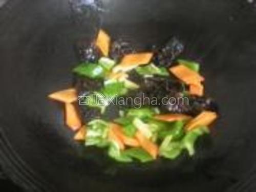 放入胡萝卜、青椒片和黑木耳煸炒。