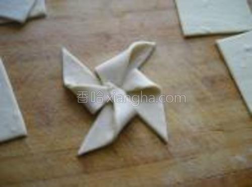 分别将四个角向中心折叠,制作成风车状。