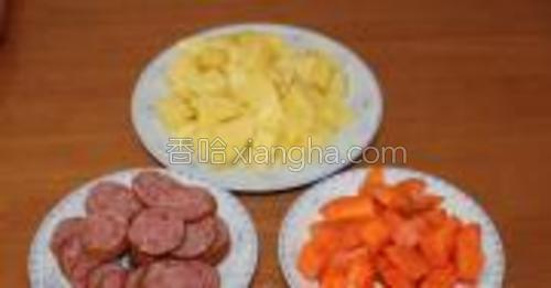 将胡萝卜、土豆、火腿肠切块备用。