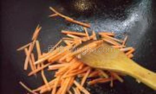 胡萝卜切丝,锅中加适量油烧热,把胡萝卜丝煸炒一下捞出。