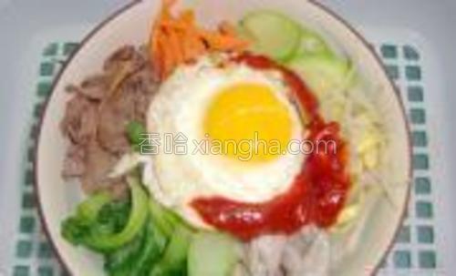 在逐个把焯好的牛里脊片,胡萝卜丝,平菇,黄豆芽,西葫芦片,油菜码放米饭上的四周,再将煎好的鸡蛋放中间,挤上韩式辣酱翻拌,开吃。
