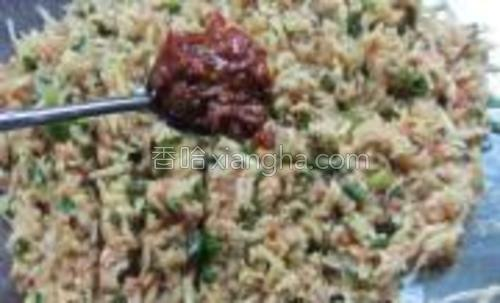 肉泥拌入土豆和葱里,放两勺蒜蓉辣椒酱,一勺植物油一起剁匀备用