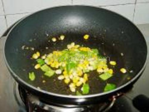 锅里继续倒入少量的油,下青椒粒和玉米粒一起煸炒,撒一点点盐,炒匀盛起。