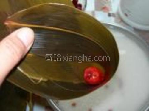 粽叶折成漏斗型,放入一颗红枣。