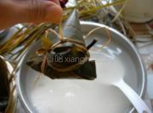 包好的粽子码入锅内,加清水没过粽子,用篦子压紧,篦子上再放置1个加满清水的盘子,加盖,电饭锅按下蹄筋/豆类开关键,自动断电后,利用余热闷一会,打开锅盖即可食用。