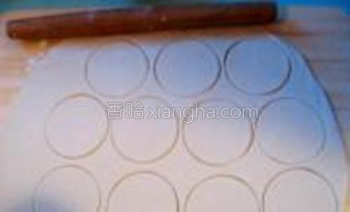 将面团擀成3毫米厚的大片,压印出圆形。