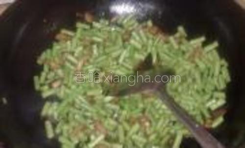 (5)将豇豆炒到八成熟,放入盐,要适当放多点,因为待会儿饭不再放盐,再加入米饭翻炒。