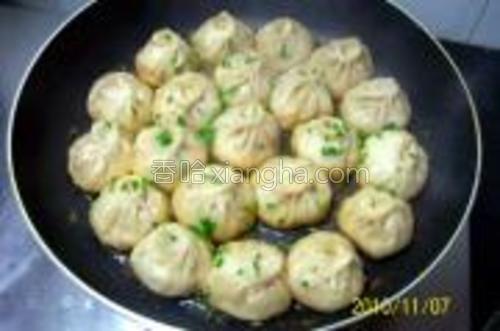 待锅内出现'吱吱'响声,清水即将收干时,打开锅盖略加煎烤,将《榨菜鲜肉生煎包》的底部煎制成金黄色即可。