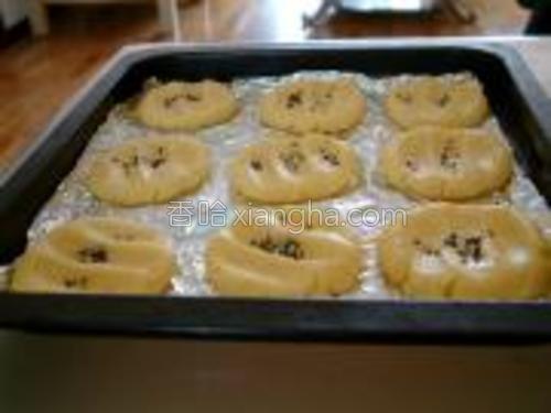 烤盘铺油纸,将面团分成小份揉成团,搓圆后按扁,按出指印,间隔均匀地码在烤盘上,撒上芝麻;