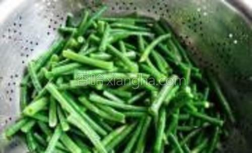将豇豆捞出,放凉开水里凉透,沥水待用。加工好的豇豆是碧绿色。