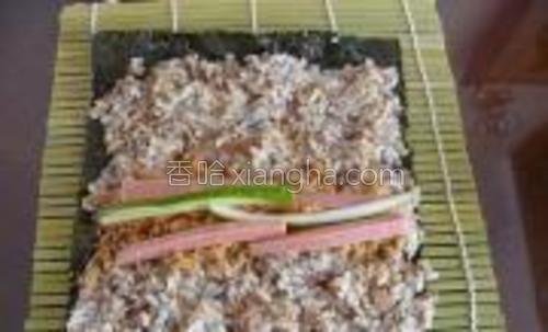 """米饭平铺在紫菜上,上端稍留些空余,以便最后的粘合。米饭直接用""""爪子""""的哈,1/4处洒上肉松,黄瓜,肉花肠"""
