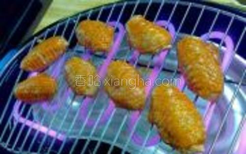 将腌制好的鸡翅放在电烤架上,烤至金黄色熟透