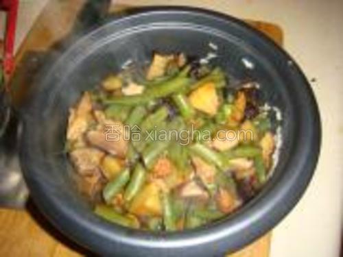 把菜和汤倒进装有米饭的电饭煲里,搅一搅。