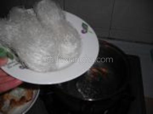 锅里水煮开,调入适量花生油、精盐,然后把粉丝放入。