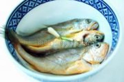 将小黄鱼置盆内,加料酒、精盐、姜片、葱段、胡椒粉腌渍15分钟左右。