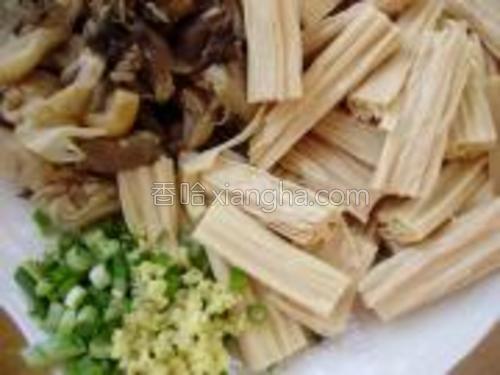 将提前焯好的鲜蘑清洗干净,同浸泡好的腐竹切成段,葱姜切成末,同放一个盘中待用。