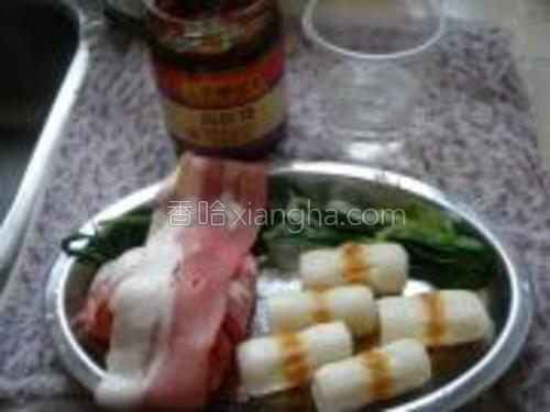 煮软的葱条挤去水份,狮子狗卷及烟肉条洗净沥水,海鲜酱凉开水备用。