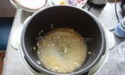 把洗净的粥米和玉米粒放到电饭煲中,加入适量的水。