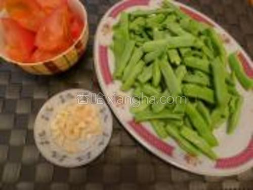 扁豆洗净去两头、去筋、掰段;番茄洗净用开水烫一下,去皮、切块;蒜切碎。