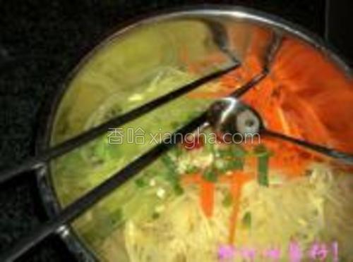将三丝放入大碗中,撒葱蒜末和小米辣,并用烧热的油浇在其上。
