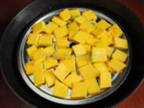 把南瓜片平铺在蒸架上。