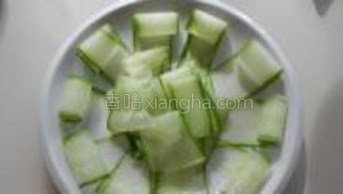把黄瓜薄片码在盘中,中间放入刨黄瓜时损坏的黄瓜片作为肉的铺垫。