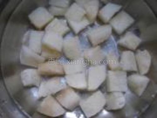 戴上手套将山药洗净切丁,放入事先准备好的水里待用。